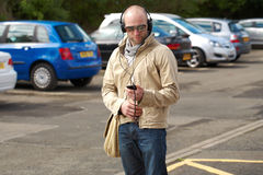 Young male in khaki listen to music, outdoor shoot Royalty Free Stock Photography