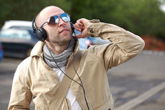 Young male in khaki listen to music, outdoor shoot Stock Photos