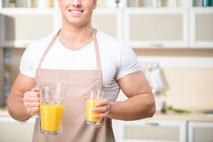 Young male kitchen worker holding a glass of juice. Vitamin drink. Nice-looking young man smiles brightly while holding a glass of orange juice and vessel Stock Photos