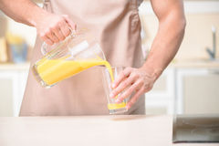 Young male kitchen worker pouring orange juice Stock Photo