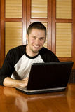 Young male on laptop smiling. At camera Royalty Free Stock Photos