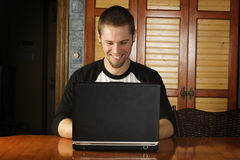 Young male on laptop smiling. Happily Stock Photography