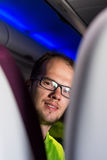 Young male looking back over passenger seats. Traveling on airplane Stock Photo