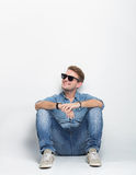 Young male looking up and sitting on the floor Royalty Free Stock Image