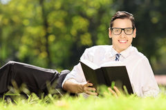 Young male lying on a grass with book and looking at camera in a Royalty Free Stock Photos