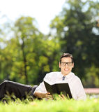Young male lying on a grass with book and looking at camera in p Royalty Free Stock Photo