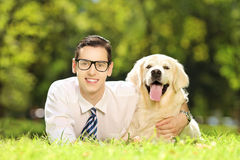 Young male lying on a grass and hugging his dog in a park Royalty Free Stock Photos