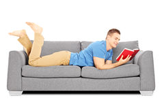 Young male lying on a sofa and reading a book Stock Images