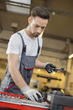Young male maintenance engineer arranging tools in drawer at car workshop Royalty Free Stock Photo