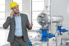 Young male manager in hard hat using cell phone by machinery in industry Stock Image