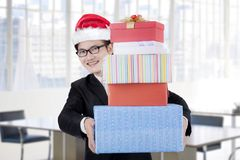 Male manager carrying Christmas gifts in the office Royalty Free Stock Photography