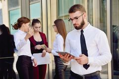 A young male manager with a tablet in his hands against the back. Ground of the girls. Office staff in the background of a multi-storey glass building. Lifestyle Royalty Free Stock Photo