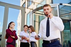 A young male manager with a tablet in his hands against the back. Ground of the girls. Office staff in the background of a multi-storey glass building. Lifestyle Royalty Free Stock Photography