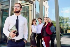 A young male manager with a tablet in his hands against the back. Ground of the girls. Office staff in the background of a multi-storey glass building. Lifestyle Stock Image