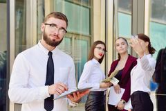 A young male manager with a tablet in his hands against the back. Ground of the girls. Office staff in the background of a multi-storey glass building. Lifestyle Royalty Free Stock Photos
