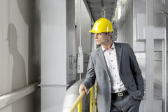 Young male manager wearing hard hat looking away in industry Royalty Free Stock Image