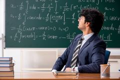 The young male math teacher in classroom. Young male math teacher in classroom royalty free stock photography