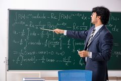 The young male math teacher in classroom. Young male math teacher in classroom stock photo