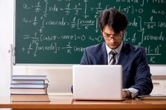The young male math teacher in classroom royalty free stock photo