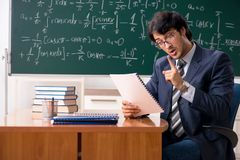 The young male math teacher in classroom. Young male math teacher in classroom stock images