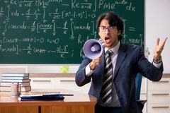 The young male math teacher in classroom. Young male math teacher in classroom royalty free stock images