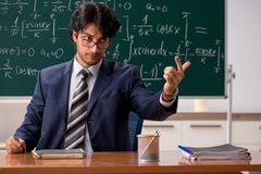 The young male math teacher in classroom. Young male math teacher in classroom stock photography
