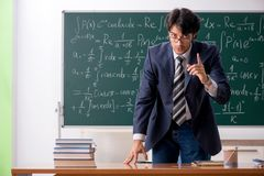 The young male math teacher in classroom. Young male math teacher in classroom stock photos