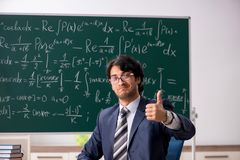 The young male math teacher in classroom. Young male math teacher in classroom royalty free stock photo