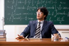 The young male math teacher in classroom. Young male math teacher in classroom royalty free stock image