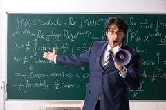 The young male math teacher in classroom. Young male math teacher in classroom royalty free stock photos