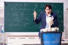 The young male math teacher and student skeleton. Young male math teacher and student skeleton royalty free stock image
