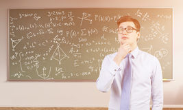 Young male math university student. Portrait of young man wearing blue tie and glasses and standing near blank chalkboard with formulas in sunlit classroom with Stock Photography