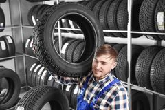 Young male mechanic with car tire. In automobile service center Royalty Free Stock Images