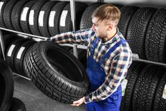 Young male mechanic with car tire in automobile   center. Young male mechanic with car tire in automobile service center Royalty Free Stock Image