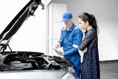 Young mechanic talking with his client. Young male mechanic checking broken car by using a tablet while talking to his client in the garage Stock Image