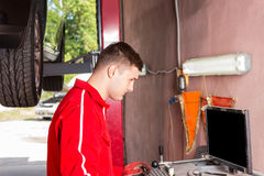 Young male mechanic checking the readout. On a computer hooked to a car elevated on a hoist as he performs a service and tune up in a garage workshop Stock Photos