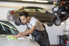 Young male mechanic cleaning car in repair shop Royalty Free Stock Photography
