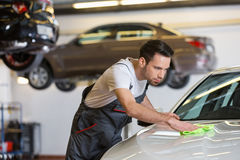 Young male mechanic cleaning car in repair shop Stock Images