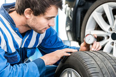Young Male Mechanic Pressing Gauge Into Tire In Garage Stock Image