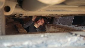 Young male mechanic underneath a car unscrewing components from under tray. Close up stock video