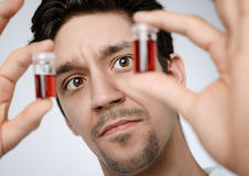 Young male medic or researcher holds up liquid samples Stock Image