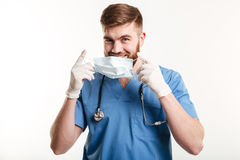 Young male medical doctor or nurse putting sterile mask. Portait of a young male medical doctor or nurse putting sterile mask isolated on white background Stock Image