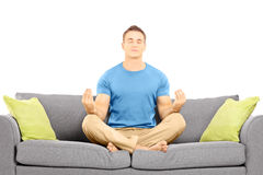 Young male meditating seated on a couch Stock Images