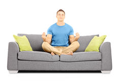 Young male meditating seated on a sofa Royalty Free Stock Image