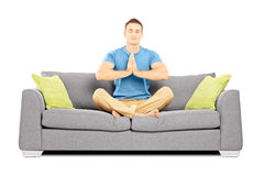 Young male meditating seated on a sofa Stock Photography