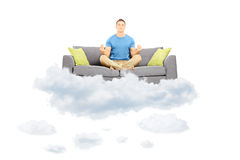 Young male meditating on a sofa and floating on a cloud Stock Photography