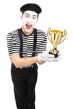 Young male mime artist presenting a trophy Royalty Free Stock Photos