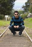 Young male model. In the rails of the train Royalty Free Stock Photography