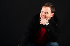 Young male model smiling and wearing a winter coat Royalty Free Stock Images