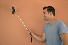 Young male model taking selfie with extending pole Stock Photos